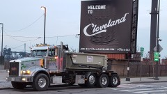 A roll off container truck posing in front of a Welcome to Cleveland sign